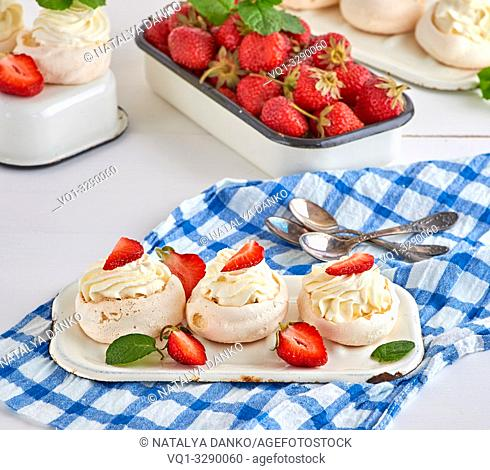 small baked round cake meringue with whipped cream and strawberry