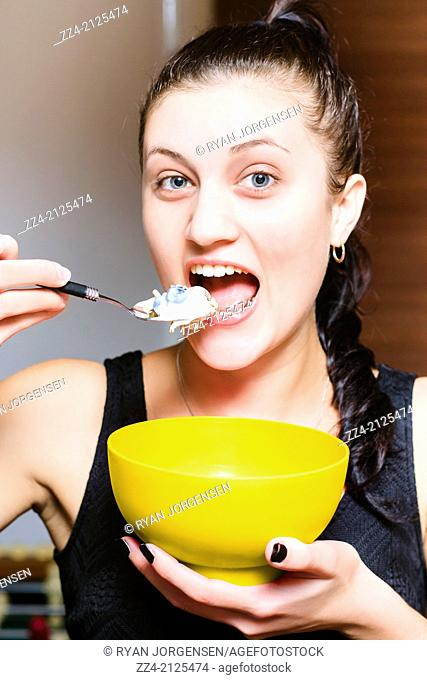 Beautiful woman with mouth open taking a bite of muesli cereal out of yellow bowl with yoghurt and blueberries