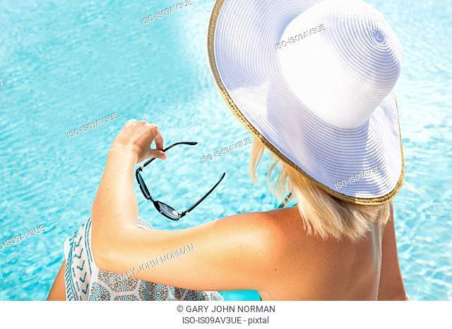High angle rear view of young woman wearing sun hat sitting by swimming pool