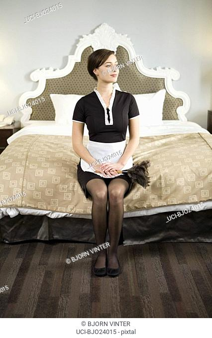 Maid sitting on edge of bed