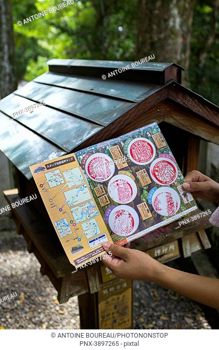 Woman on Kumano Kodo pilgrimage trail showing all of her collected stamps on the way to Kumano Hongu-taisha Shrine, Tanabe City, Wakayama Prefecture, Japan