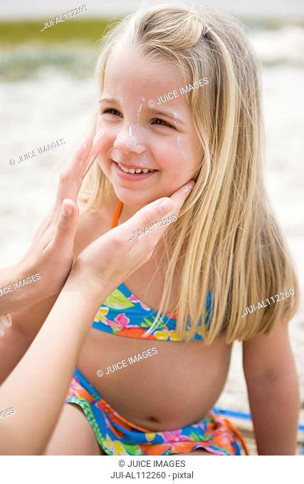 Mother applying sunscreen to daughter, smiling