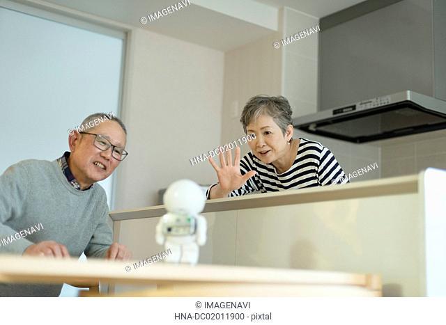 Senior couple talking to robot