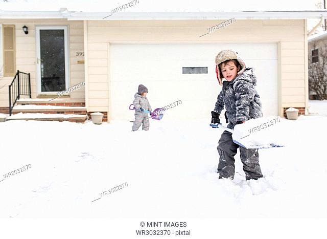 Boy wearing furry hat and girl standing in a snow covered driveway, shovelling snow