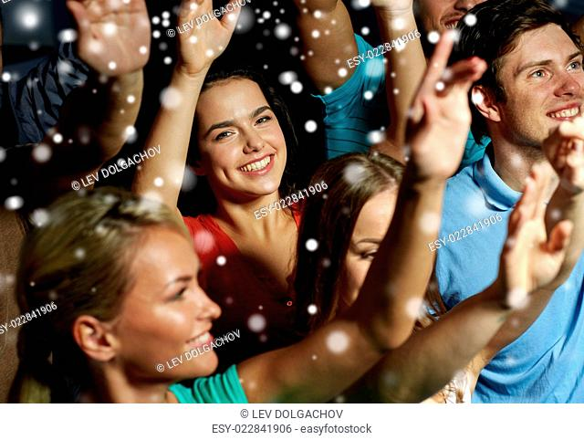 party, holidays, celebration, nightlife and people concept - smiling friends waving hands at concert in club and snow effect