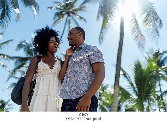 USA, Florida, Miami Beach, happy young couple at palm trees in summer