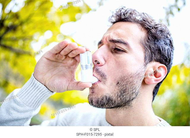 MODEL RELEASED. Young man using asthma inhaler, close-up