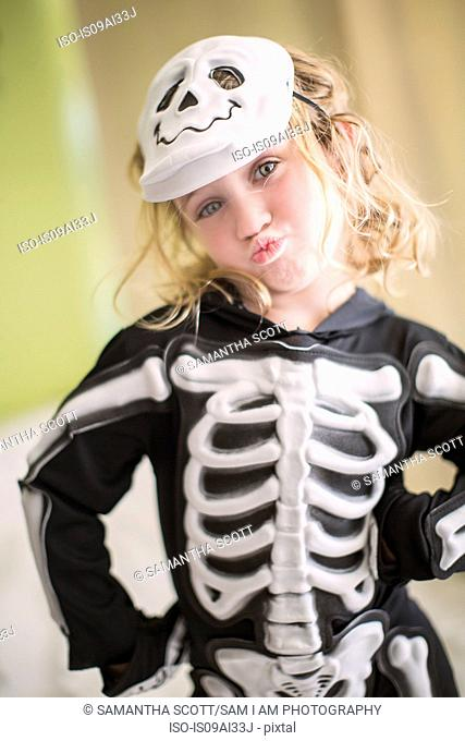 Portrait of young girl in skeleton costume with skull mask