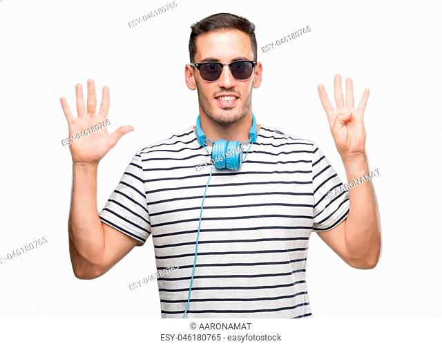 Handsome young man wearing headphones showing and pointing up with fingers number nine while smiling confident and happy