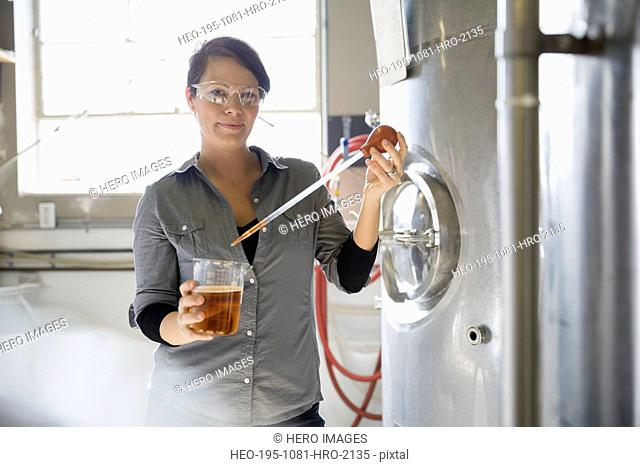 Brewery worker extracting beer from beaker with dropper