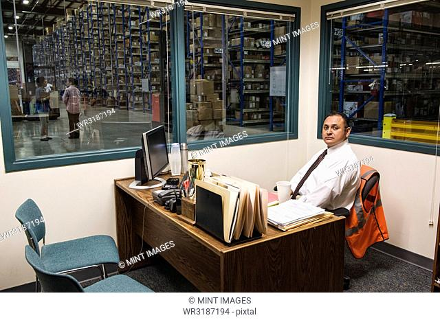 Portrait of a male Hispanic American executive in an office in the middle of a large distribution warehouse full of racks of products stored in cardboard boxes...
