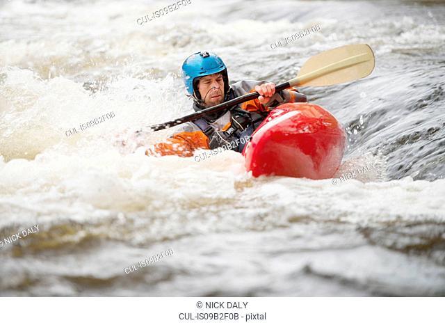 Imbalanced male kayaker paddling River Dee rapids