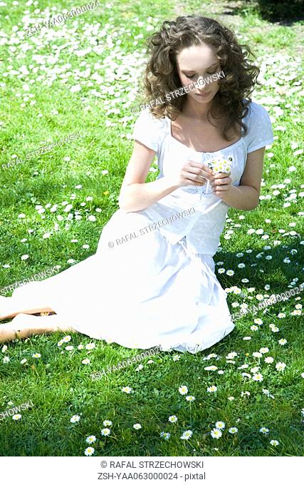 Young woman sitting in meadow, holding flowers, high angle view
