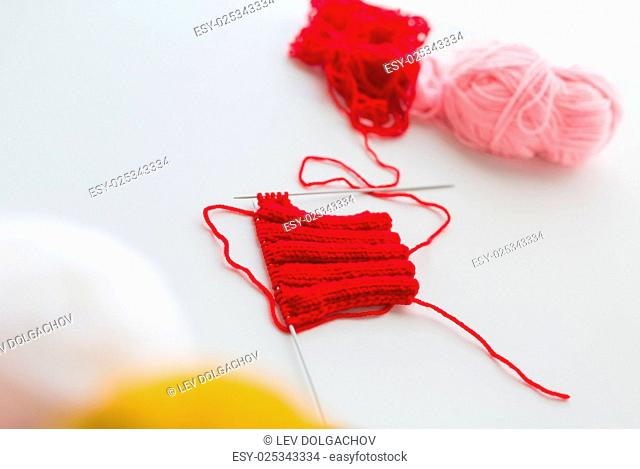 handicraft and needlework concept - hand-knitted item with knitting needles