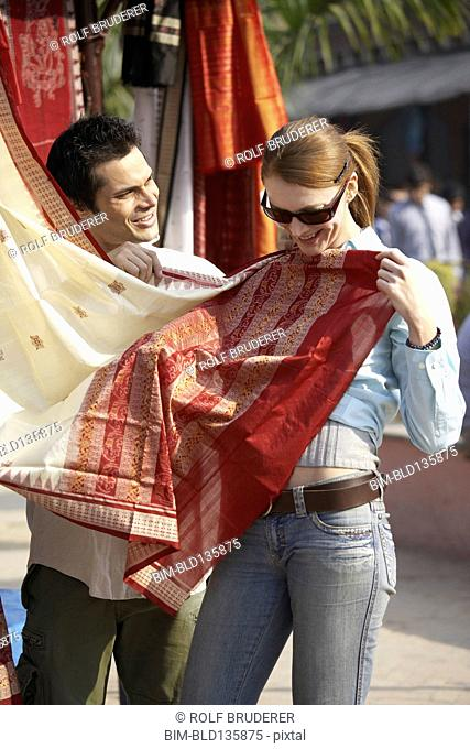 Couple admiring fabrics at outdoor market