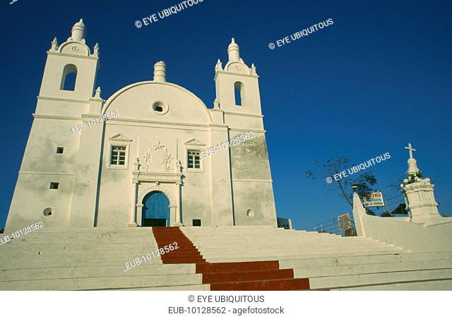 Church of St Thomas. White painted exterior facade with painted red central strip leading up steps to blue door of entrance