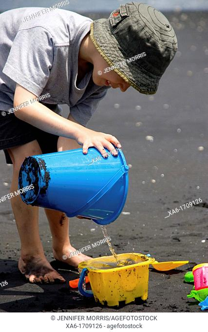A young boy plays on the beach with water and buckets