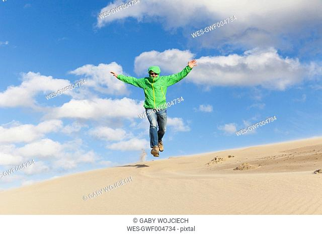 Enthusiastic mature man jumping over sand dune