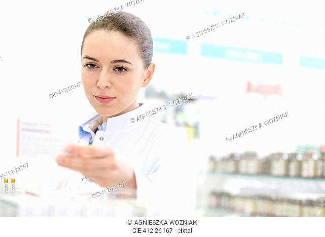 Pharmacist reading label on box in pharmacy