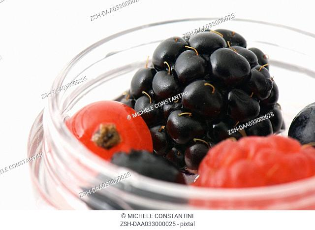 Berries in small cosmetic container, close-up, cropped