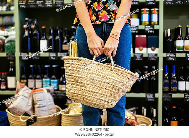 Mid section of customer holding basket in a store