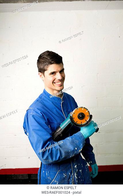 Portrait of smiling construction worker holding an angle grinder