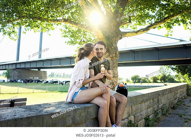 Happy couple sitting on a wall in summer eating ice cream