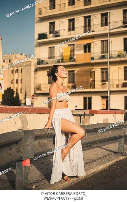 Teenage girl weraing long skirt and bikini top, posing in the street
