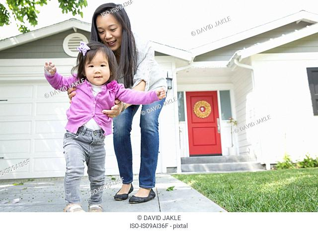Mid adult woman and female toddler taking steps