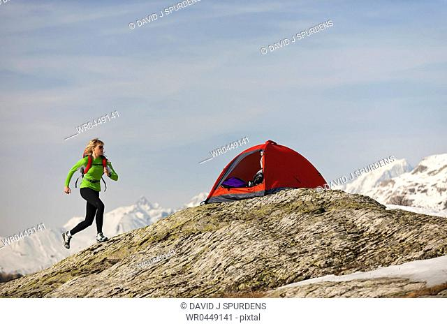 A woman runs back to her tent in high altitude mountains