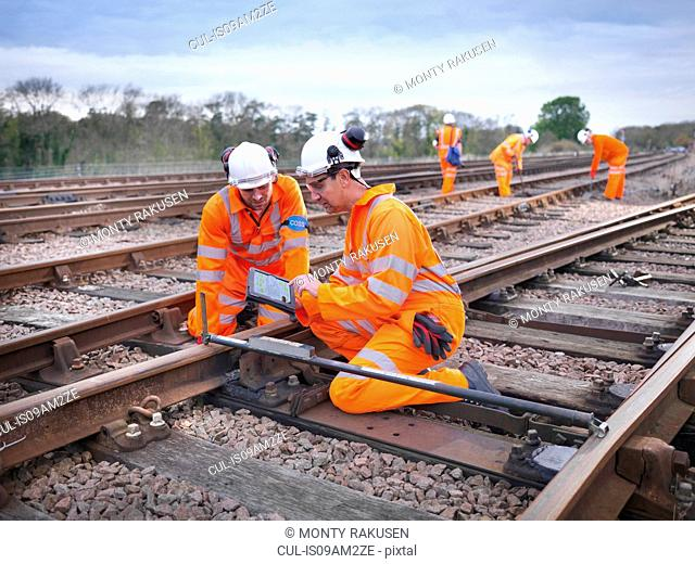 Railway maintenance workers measuring track and recording notes on digital tablet