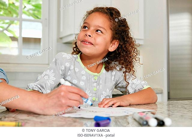 Girl at kitchen counter using felt tip pen to draw picture, looking up smiling