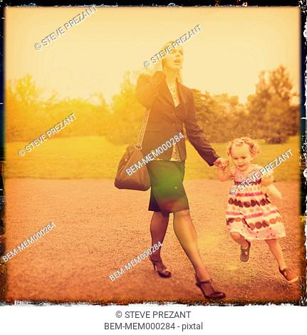 Caucasian mother and daughter walking and holding hands