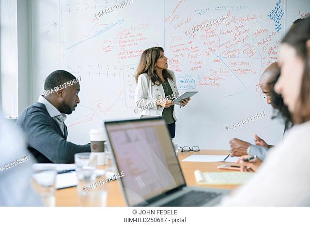 Businesswoman holding digital tablet near whiteboard in meeting