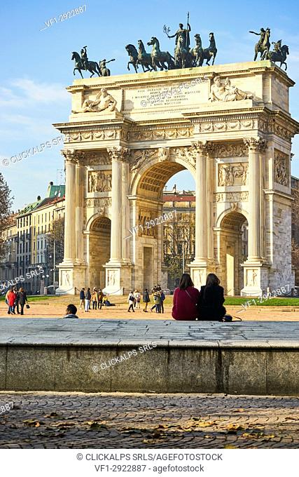 Milan, Lombardy, Italy. Girls are sitting in front the Arch of the Peace