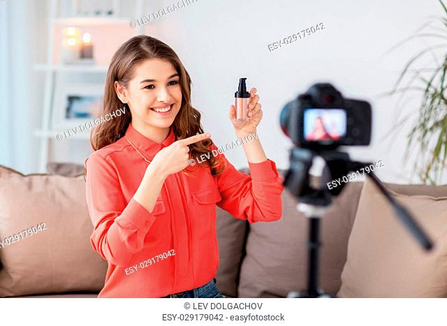 blogging, technology, videoblog, makeup and people concept - happy smiling woman or beauty blogger with foundation and camera recording tutorial video at home