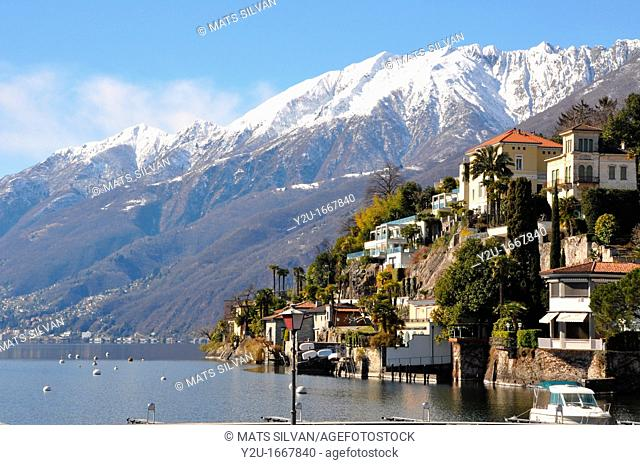 Village on the lakefront and snow-capped mountains