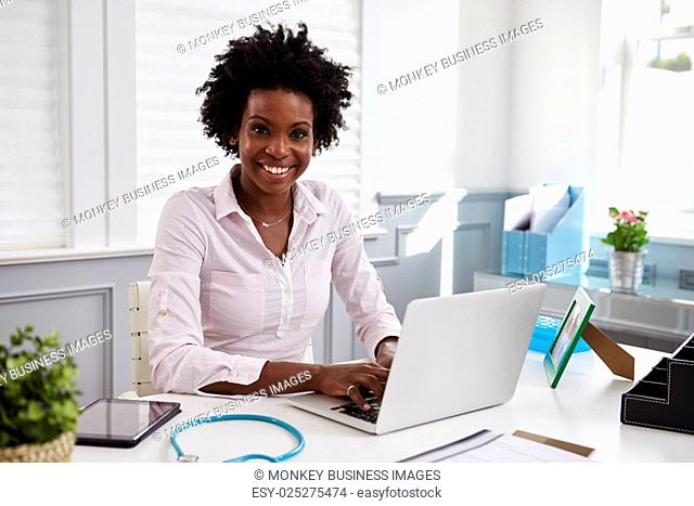 Black female doctor at work in an office, looking to camera