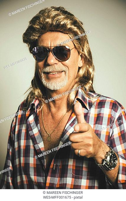 Portrait of smiling man wearing sunglasses and blond wig showing thumbs up