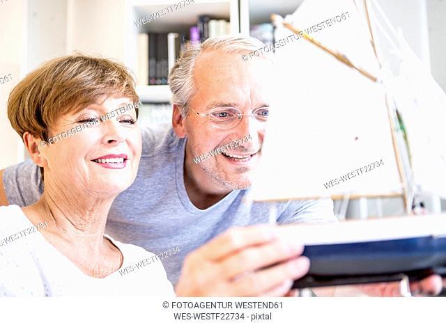 Senior couple looking at model ship