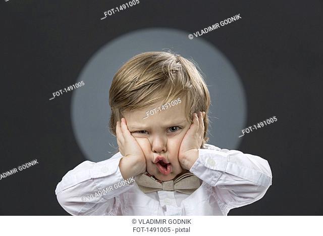Portrait of cute boy pressing cheeks against gray background