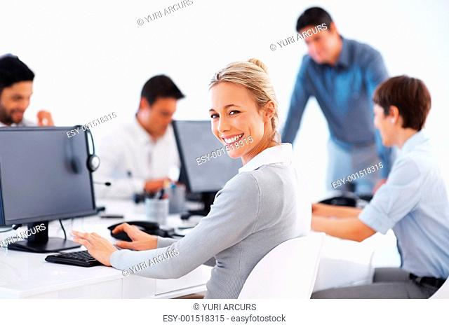 Smiling business woman working on computer with colleagues in background