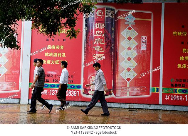 Men walking past a huge advertisement while walking down the street together in Beijing, China