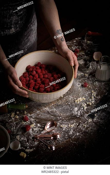 Valentine's Day baking, woman preparing fresh raspberries in a bowl
