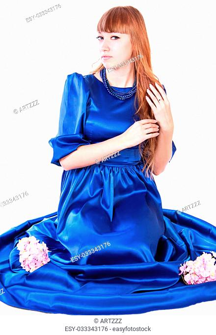 Young attractive woman sitting in a long blue evening dress isolated over white background