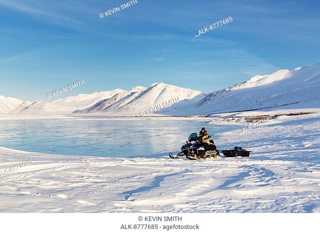 Man riding a snowmachine stops in front of overflow ice on the frozen Anaktuvuk River, Napaktualuit Mountain in the background