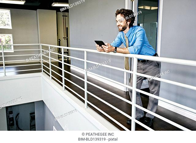 Caucasian businessman using digital tablet at railing