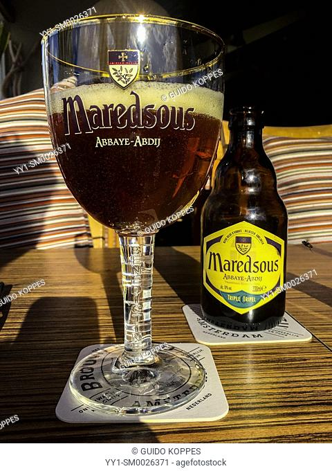 Hoek van Holland, Netherlands. Glass and bottle of craftbeer on a sunny table inside a beach house
