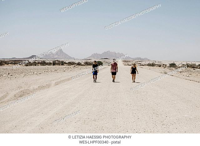 Namibia, friends walking on the road to Spitzkoppe