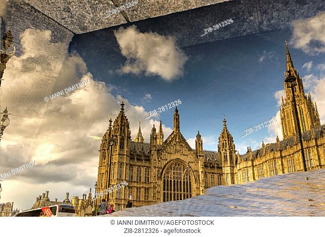 UK,England,London,Westminster-Houses of Parliament reflected on the wet pavement